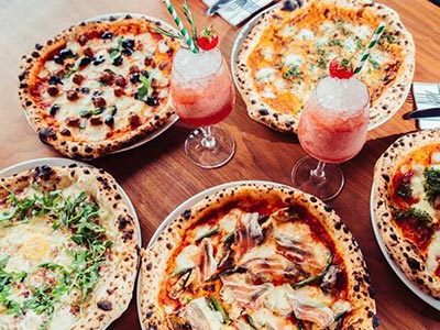 Two cocktails on a table surrounded by plates of pizza