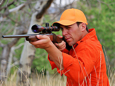 A man wearing an orange shirt aiming a hunting rifle