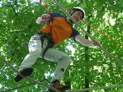 Image of a man attached to a harness climbing along a rope while holding onto a rope