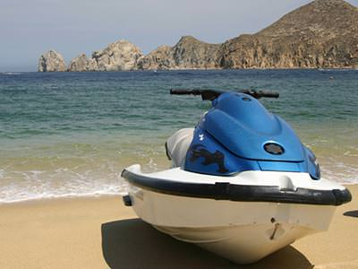 Image of a jet ski on the sand with the ocean water behind