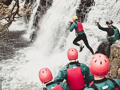 Image of a group of people jumping into the water with an instructor guiding them