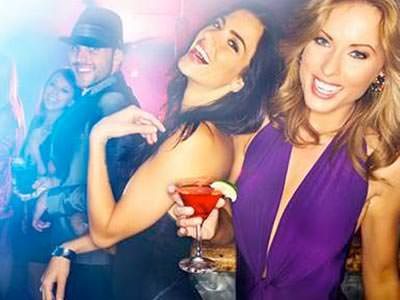 Image of women glammed up drinking cocktails standing next to a guy wearing a black coat and black hat