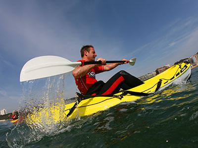 Image of a man in a yellow Kayake in the ocean with a paddle wearing a life jacket