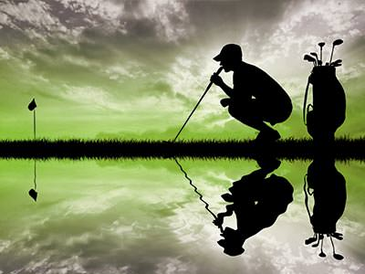 The silhouette of a man crouching next to a bag of golf clubs, mirrored horizontally against water