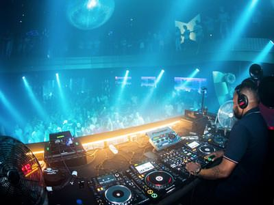 Image of a dj playing music to a packed nightclub with blue strobe lighting shining onto the crowd with a big disco ball above them on the ceiling