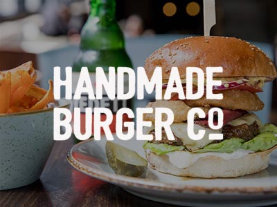 Image of a burger filled with cheese and lettuce and onion rings on a plate with a wooden stick through it with a bottle of beer and a bowl of chips with the handmade burger logo