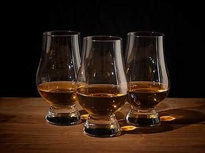 Image of three whiskey glasses filled with whiskey placed on a wooden table
