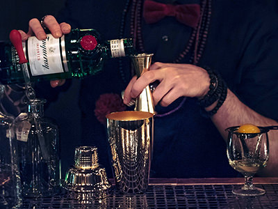 A man pouring gin into a cocktail glass
