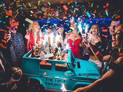 A group of people standing around a drinks table that is in the shape of a small car, while confetti falls from the ceiling