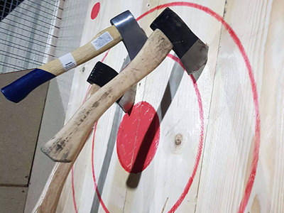 Three axes sticking out of a target on a wooden board