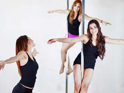 Two women posing on pole-dancing poles, with another woman posing at ground level