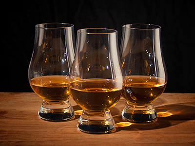 Three whisky tasting glasses partially filled with whisky
