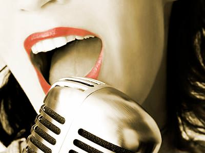A close up of a woman's mouth singing into a microphone