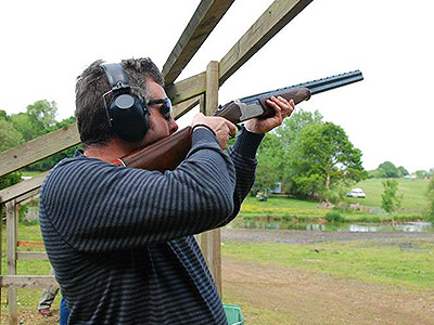 A man holding a rifle and aiming it towards the sky