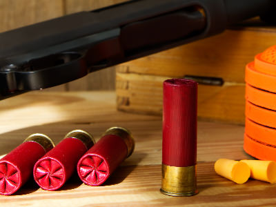 Bullets in the foreground, to a backdrop of a gun and some clays