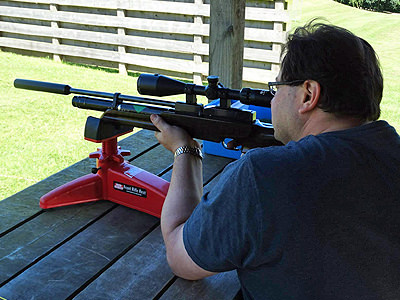 The back of a man aiming with an air rifle set on a red stand, on a table