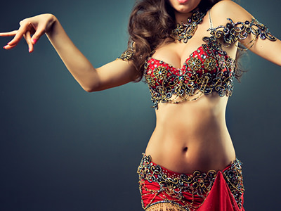 A woman posing in a traditional belly dancing outfit