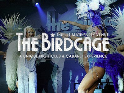 Three men in costumes and feathered head dresses on stage, pointing towards the front, with The Birdcage logo over