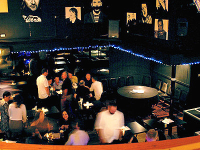 Interiors of comedy club with images of comedians on the wall