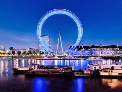 The London Eye at night, with the River Thames in the foreground