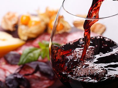 An image of food overlaid with a wine glass being filled with red wine