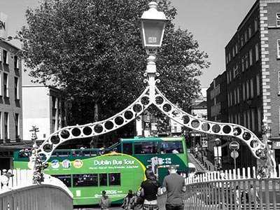 A colour graded image of a green Dublin sightseeing bus against a black and white Dublin street scene
