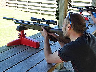 A man aiming a rifle down a range