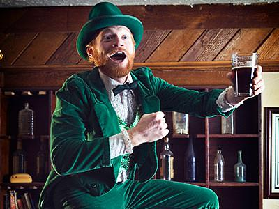 A man in a leprechaun outfit posing with a glass of beer