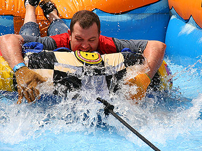 Man getting a face full of water as he slides on an inflatable dinghy