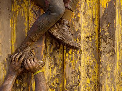 A person's muddy hands pushing another person's muddy legs over a wall