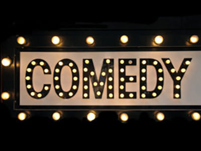 The word 'comedy' illuminated in lights