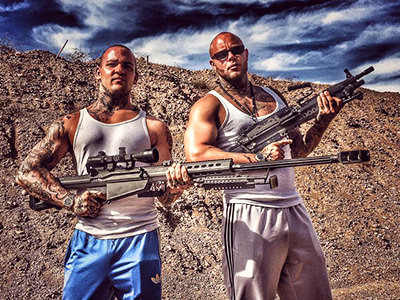 Two men posing with very large machine guns