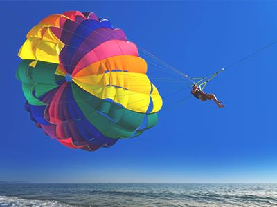 A person parasailing over the sea with a multicoloured parachute against a cloudless blue sky