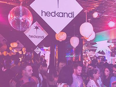 A group of people standing under purple lights and 'hedkandi' signs