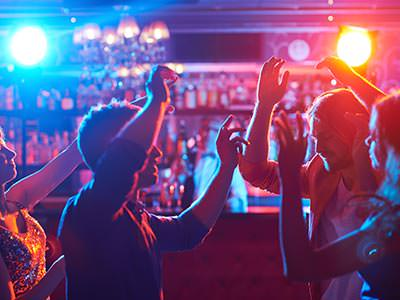 People dancing in Lava Lounge, with blue and yellow lights behind them