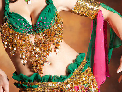 A close up of a woman in a jewelled bikini style green and gold top, and a matching sari bottom