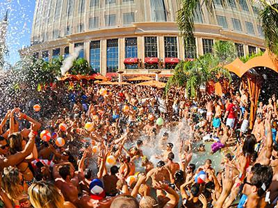 A large group of people dancing in and around a pool and under white confetti at a daytime pool party