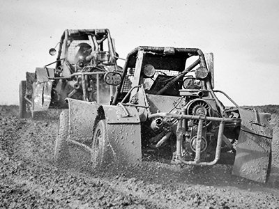 Black and white image of a line of rage buggies, driving through a field