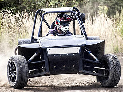 A man driving a rage buggy through a field