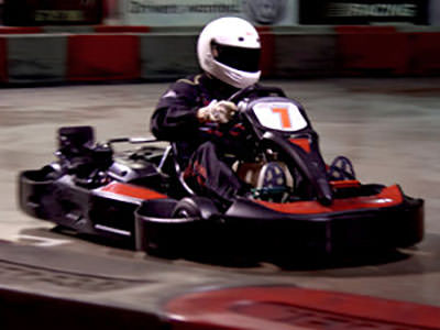 A man racing a go kart on an indoor karting track