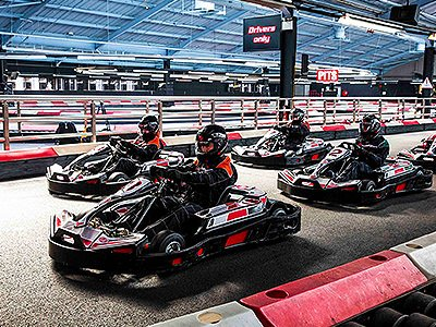 People in go karts on an indoor track, lined up and ready to race
