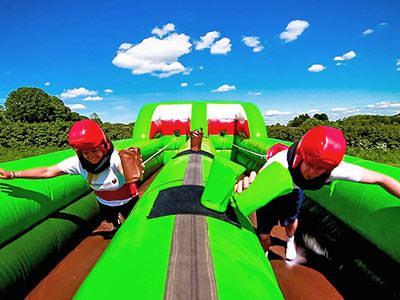 Two people racing down a green inflatable