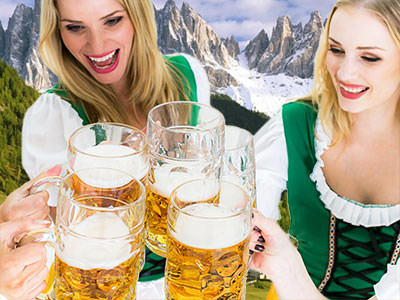 Two women dressed as Bavarians, clinking their steins together