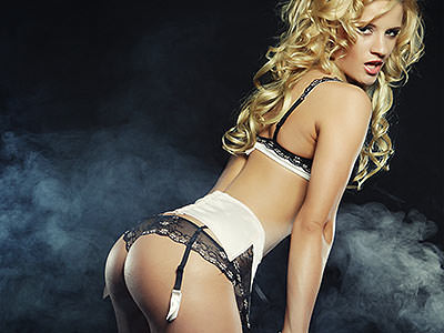 A woman bent over in white underwear and suspenders to a smoky backdrop