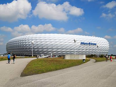 White exterior of the Allianz Arena, with grounds and people in foreground