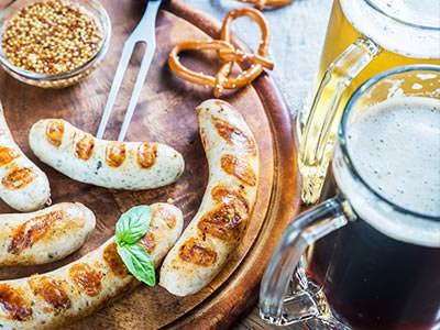 Bratwurst and various other German foood on a wooden board, with two full steins on the side