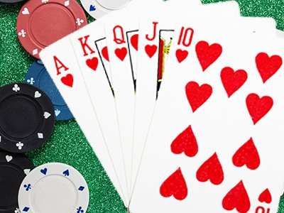 Five red playing cards and casino chips on a green surface