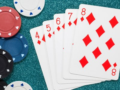 Five red diamond cards next to poker chips
