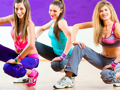 Three women in exercise gear, crouching down to a purple backdrop