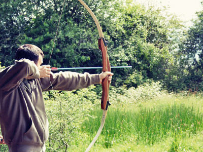 A man firing a bow and arrow in a field